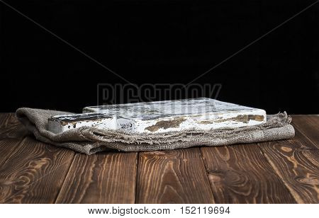Dark background for product montage. Old wooden cutting board with tablecloth and black background