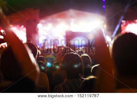 Silhouettes of concert crowd in front of bright stage lights. Night shot
