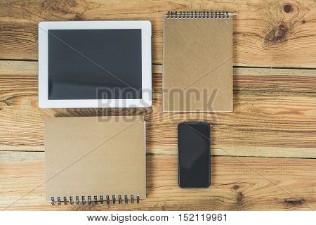 Close up of tablet, writing-pad and smartphone on table