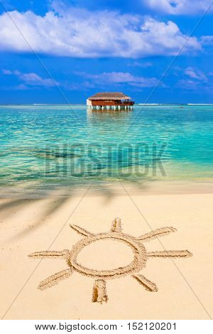 Drawing sun on beach - concept holiday background