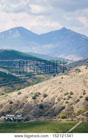 Silent scenic terrain, hills, mountains and lonely house