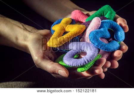 Bunch Of Multi-colored Numbers Of Felt In The Palms