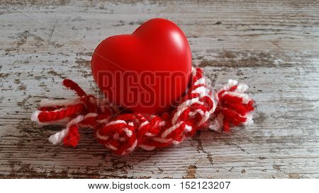 Warm your heart! Red heart with handmade knitted scarf on old wooden background