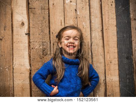 Little Girl In Stylish Clothes And A Beautiful Wooden Background