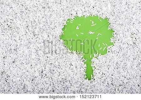 simple green tree symbol made inside of shredded paper heap