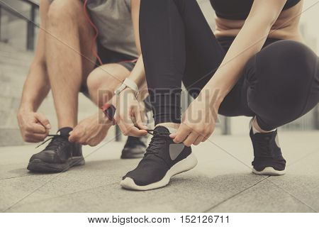 Be ready. Active athletic man and cheerful young woman wearing sportswear and tying their shoelaces while preparing for the training.