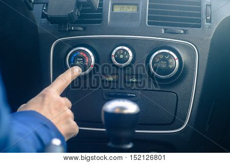 Young man is turning on car air conditioning system