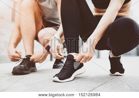 Step forward. Young active woman and man tying their shoelaces while preparing for the training and spending time together.