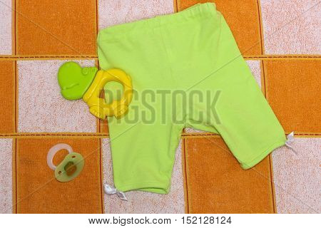 Green pants with white ribbons , green Hippo teether,  orthodontic nipple.Clothes for baby close up. Things for babies in orange and white plaid .