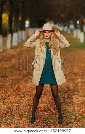Beautiful elegant woman standing full length in fashionable beige hat in a park in autumn.