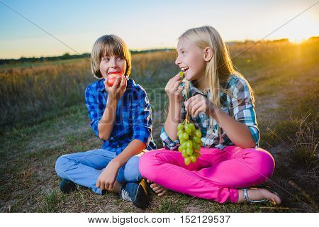 Little girl and boy eating fruits outdoor. Healthy nutrition concept.