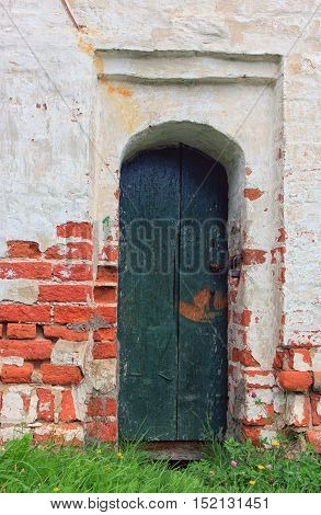 facade wall from red brick blocks with old green wooden board door with padlock of old medieval church Russia