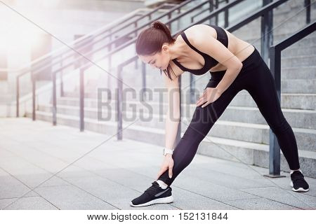 Way to keep fit. Pretty young flexible girl wearing a sportswear and doing stretching exercises while waiting for training.