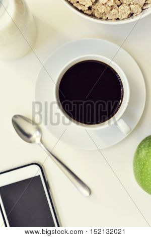 high-angle shot of a white table set for breakfast with a green apple, a cup of coffee and a bowl with cereals, and a smartphone