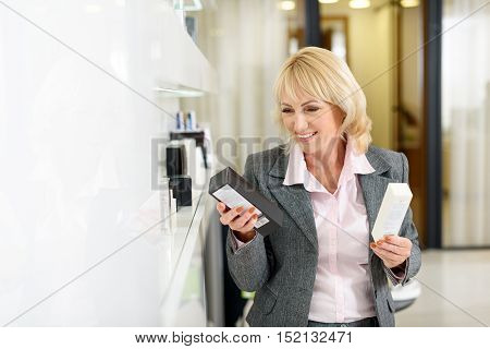 Puzzled mature woman is choosing between two cosmetic products. She is holding to boxed and looking at it pensively. Woman is standing in store and smiling