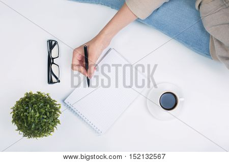 Top view of woman's hand writing in notepad placed on white surface with coffee cup and other items. Mock up
