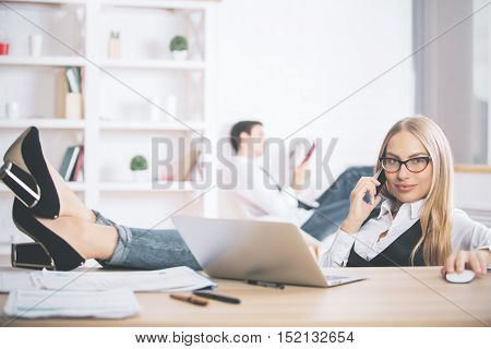 Portrait of beautiful young businesswoman with feet on table talking on cellular phone and using laptop
