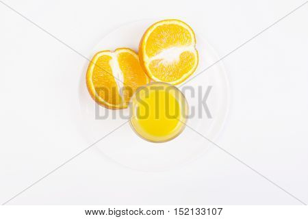 Top view of white desktop with orange halves on plate and juice