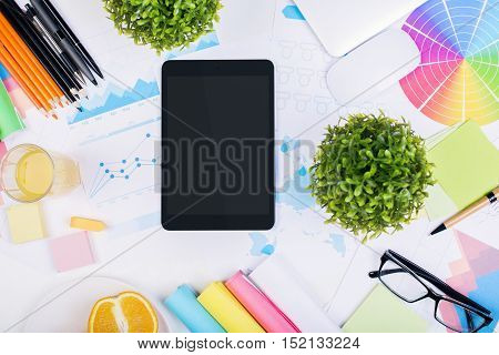 Top view of creative messy desktop with blank tablet orange half colorful supplies decorative plants and other items. Mock up