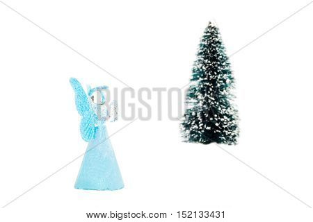 Blue glass angel praying near christmas tree on white background