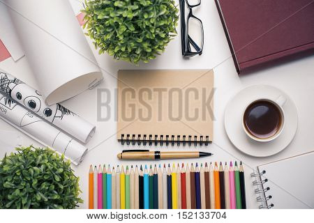 Top view of workplace with blank spiral notepad coffee cup colorful supplies decorative plants and other items. Mock up