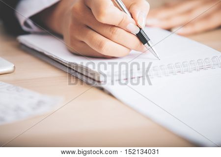 Closeup of young woman's hand writing in spiral notepad placed on light wooden desktop