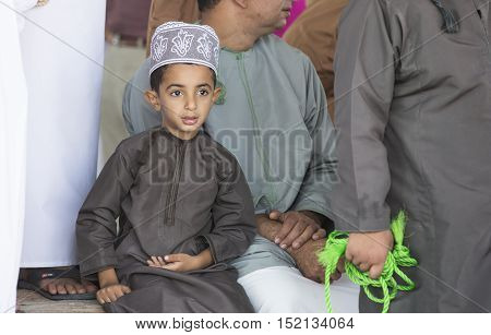 Nizwa Oman October 13th 2016: young omani boy in traditional outfit in a goat market
