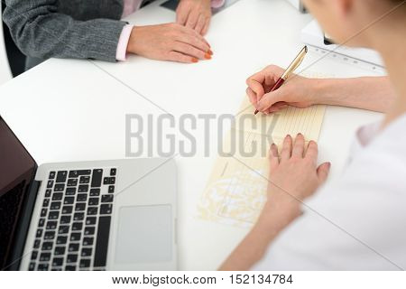 Close up of doctors arms writing diagnosis for woman at clinic
