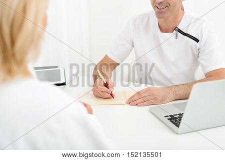 You are healthy. Experienced general practitioner is diagnosing mature woman. Man is sitting at desk and smiling