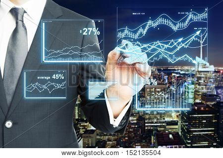 Closeup of businessman's hand drawing digital business charts on night city background. Finance concept