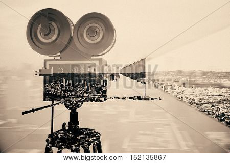 Retro movie camera on abstract city background. Double exposure. Cinema concept. Vintage filter