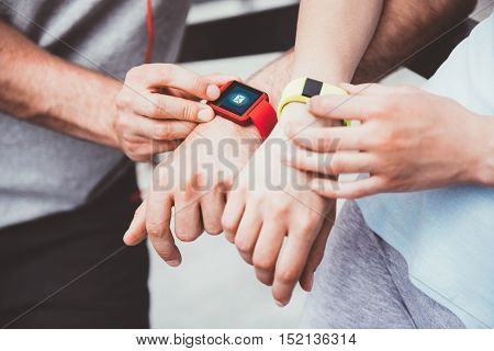 Sharing sports performance. Athletic and sporty couple looking at their smartwatches and sharing data after working out.