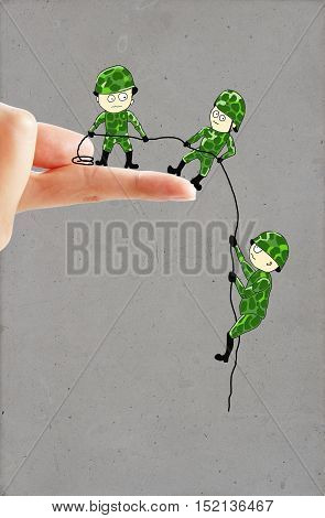 Creative drawing of small soldiers on real human hand helping each other descend down a finger using a rope