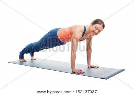 Smiling woman doing Ashtanga Vinyasa yoga asana Utthita chaturanga dandasana (or phalakasana) - extended four-limbed posture plank pose isolated on white background