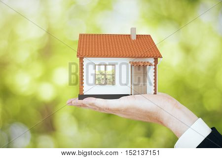 Hand holding small house model on blurry green background. Real estate property and mortgage concept. 3D Rendering