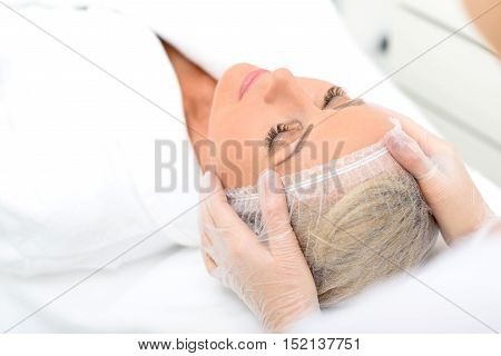 Skillful beautician is examining female facial skin before treatment at wellness center