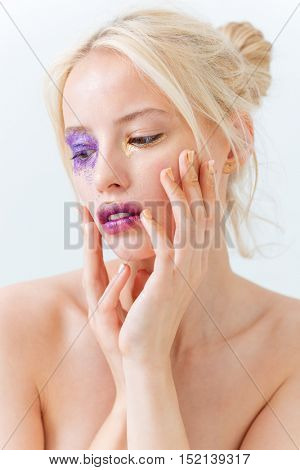 Beauty portrait of sensual young woman with creative makeup touching her face over white background
