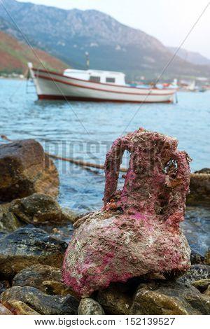 old amphora on stones, near the sea
