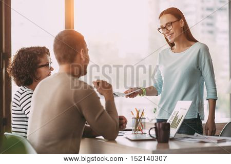 That is for you. Pleasant smiling woman giving paper to her colleagues who is sitting at the table while working in the office