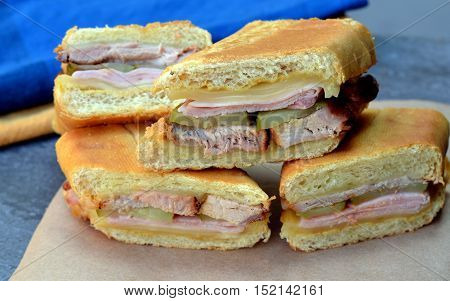 Close up of Cuban Sandwiches (Cubanos): Shown on brown paper with napkins in the background.