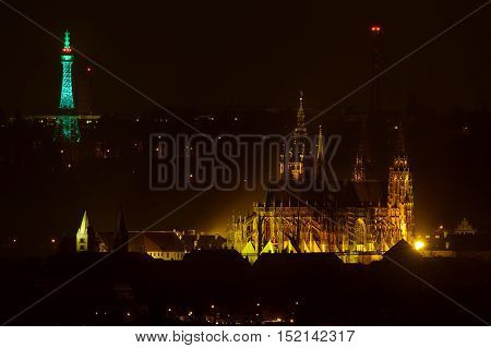 Prague castle with cathedral of saint vitus with Petrin lookout tower in green Saint Patrick day color in background. Famous travel destination in the middle of Europe