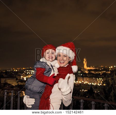 Mother And Daughter In Christmas Hats Showing Thumbs Up, Italy