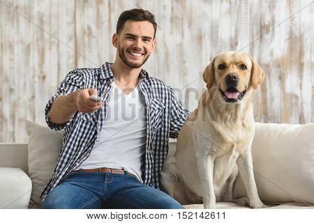 happy smiling man sitting with his dog with remote controller