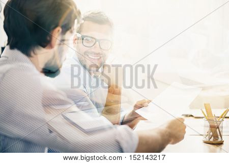 Eye contact. Young-looking bearded man with glasses discussing important business deals with his partner in light modern office.