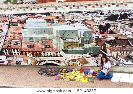BOGOTA COLOMBIA - APRIL 21: Street vendor selling souvenirs texts on her phone in Bogota Colombia on April 21 2016