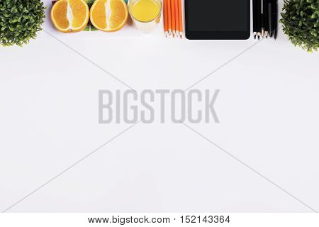 White desktop with oranges decorative plants supplies and tablet. Mock up