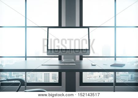 Closeup of modern workplace with blank white computer screen keyboard notepad and other items in interior with large windows and city view. Mock up 3D Rendering
