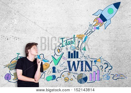 Side view of casual young guy pointing at creative rocket ship sketch on textured concrete wall background. Start up concept