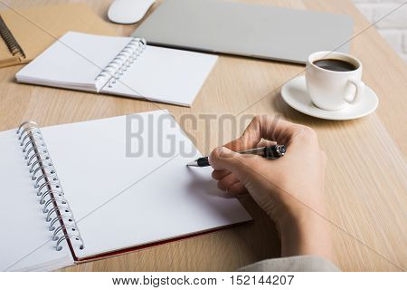 Side view of woman's hand writing in blank spiral notepad placed on wooden desktop with pencils closed laptop and coffee cup. Mock up
