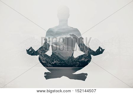 Meditating businessman silhouette on landscape background. Relaxation concept
